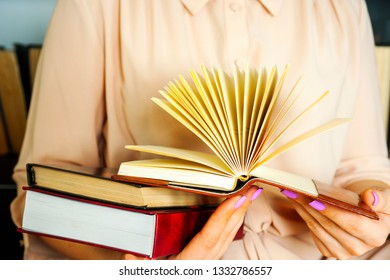 Young girl in a light dress is reading a book. Female hands hold a book in their hands.