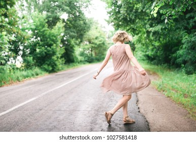 A young girl in a light dress turns in a dance near the road. Blonde with a cut of the square.