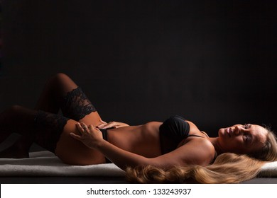 A young girl in lingerie is lying in front of a camera