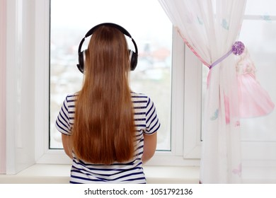 Young girl is listening to music with headphone and looking in window.
