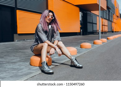 Young girl listening music in headphones, urban street style,outdoor street style hipster dj woman in yellow sunglasses and dj headphones listen music and smile, orange, crazy style, street shoot,
