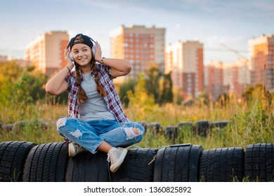 young girl listening music headphones, urban street style, outdoor street style hipster dj woman in black cap headphones dj listening to music and smiling, orange, crazy style city background, sunset