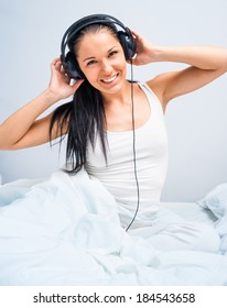 young  girl listening to music at home in white bed