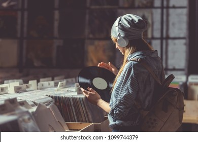 Young girl listening to music on headphones in music store