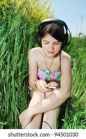 A young girl listening music in a spring field