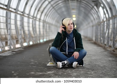 Young girl listens to music in big headphones in the subway tunnel