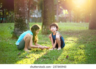 Young girl with a little brother playing in the garden during at sun down. Concept of happy sibling.