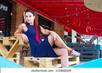Young girl with a lock of red hair sitting in a street cafe