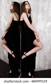 Young girl with long beautiful hair and smoky eyes wearing black maxi evening dress posing with a mirror.