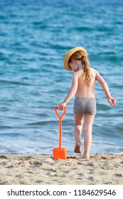 Young girl with long blonde hair wearing a hat playing at the beach with red sand shovel and blue sea waves in the backgroun