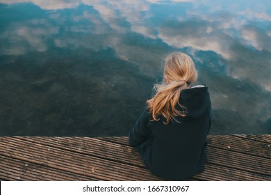 young girl with long blonde hair is sitting on a wooden stage looking in clear shallow water with reflecting cloudy sky in a thoughtful pose - coming of age, sadness and sorrow concept