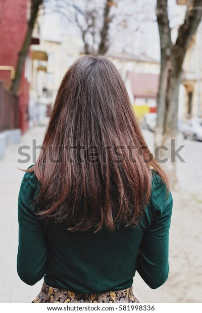 Young girl with long dark hair on a walk in the park. Brunette with straight dark hair on the street.