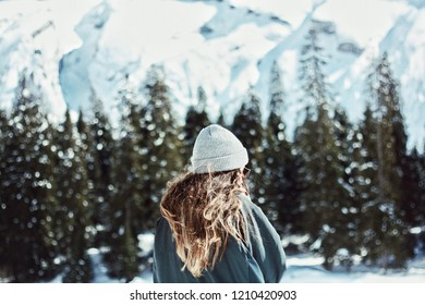 young girl with long hair and beanie hat in beautiful winter setting