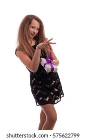 Young girl with long hair in black dress with holiday gifts in hands on a white background in studio