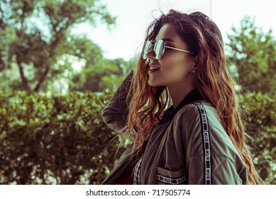 young girl with long hair poses outdoors,looks with a smile into the distance, model is dressed in a stylish jacket, sunglasses, on a background of green crowns of trees