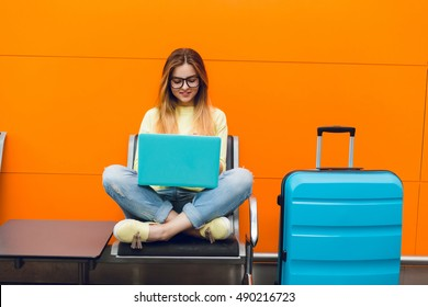 Young girl with long hair is sitting on chair on orange background. She wears yellow sweater and jeans. She is typing on laptop.