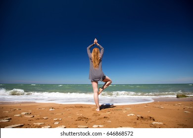 A young girl with long hair sitting on the ocean and doing yoga, she is relaxed and meditates.