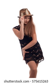 Young girl with long hair wearing a black dress and gold hat on a white background in studio