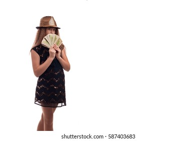 Young girl with long hair wearing a black dress and gold hat with money in hand on white background in studio