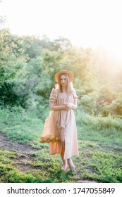a young girl in a long linen dress, a summer photo shoot, a girl in the forest, a hairstyle with a bow, a string bag with lemons, a girl with a bag and lemons