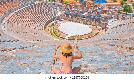 Young girl looking at Amphitheater in Ephesus  - Young girl sunbathing and sitting Amphitheater - Ephesus, Turkey