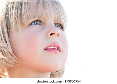 Young girl looking up in awe on white background