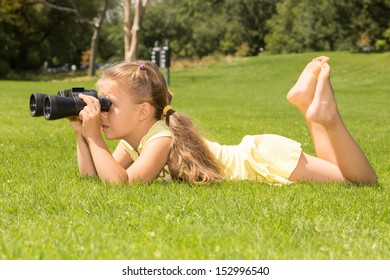Young girl looking in binoculars while lying on her belly on a green lawn