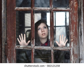 Young girl looking at the camera through the glass of the old windows