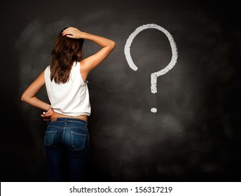 young girl looking chalkboard with interrogation symbol