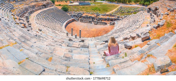Young girl looking at Roman amphitheater in ancient city - Young girl sunbathing and sitting Amphitheater - Ancient roman amphitheater at Miletus in southern Turkey