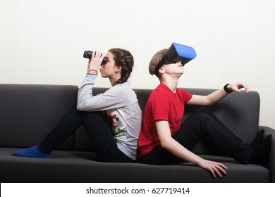 Young girl looking thorough the binocular and the boy wearing virtual reality 3D glasses, sitting on the sofa. Different point of view concept.