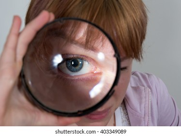 A young girl is looking through a big magnifier closeup