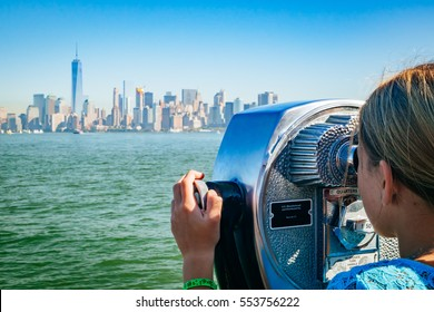 Young girl looking through binoculars at the Manhattan New York City Skyline from Liberty Island. The background shows the lower Manhattan and the financial district, including the Freedom Tower.