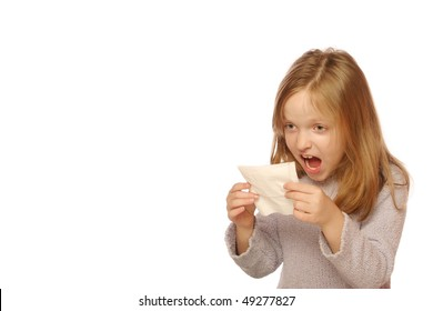 Young girl looking at tissue after blowing her nose