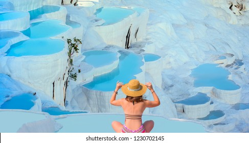 Young girl looking at travertine pools and terraces in Pamukkale -  Young girl sunbathing and sitting front travertine pools - Cotton castle in southwestern Turkey