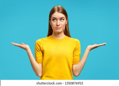 Young girl looks aside and and spreads hands. Photo of attractive girl shows open palms with something in yellow sweater on blue background