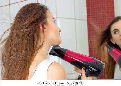 a young girl looks in the mirror and dries hair