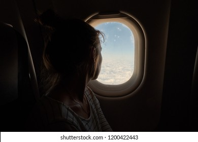 A young Girl looks out the window of the plane. The passenger looks out the window of the plane.