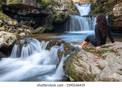 Young girl looks at Puente Ra waterfall, La Rioja, Spain