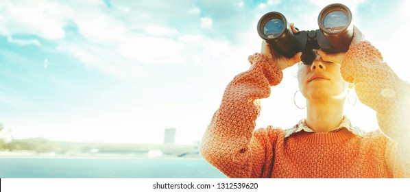 Young girl looks through binoculars at the sea on a bright sunny day. Travel Concept