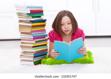 Young girl with lots of books reading on the floor