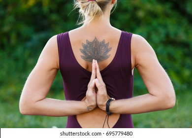 Young girl with lotus tattoo doing yoga or fitness exercise outdoor in nature with beautiful sky landscape, Namaste pose. Meditation and Relax, freedom concept, back view