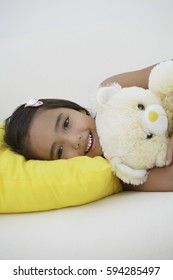 A young girl lying down with her teddy bear