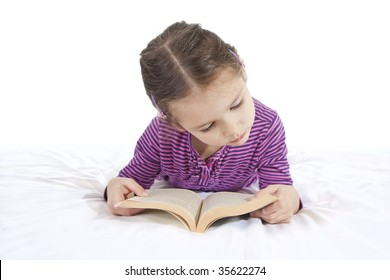 Young girl lying down and reading book on white