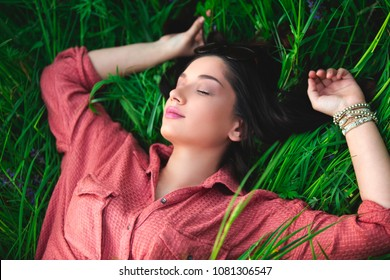 Young girl lying in grass with closed eyes day dreaming. Close up from above with copy-space. Sleep and dreaming concept.
