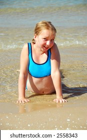 Young girl lying on a beach in shallow water