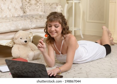 Young girl lying on a carpet with a laptop