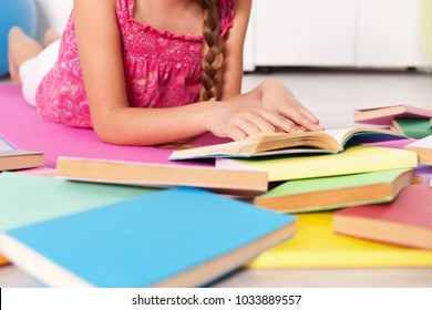 Young girl lying on the floor with lots of books - closeup, shallow depth