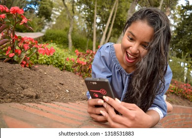 Young girl is lying on the floor in the middle of a park while reading some messages on her smart cell phone that cause great amazement.