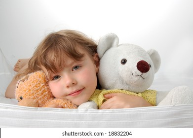 Young girl lying on the floor with two teddy bears. Smile face